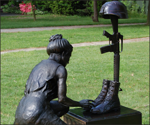 Gold Star memorial woman kneeling at battle soldiers cross